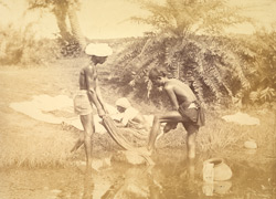 Washermen at work beside a river or pond